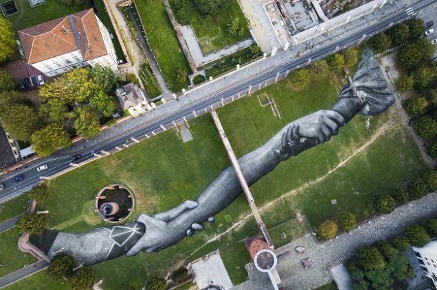 Фреску с гигантским рукопожатием нарисовали на траве в Турине